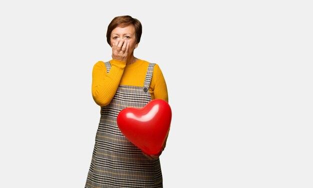 Mittlere gealterte frau, die den valentinsgrußtag sehr erschrocken feiert und angst versteckt