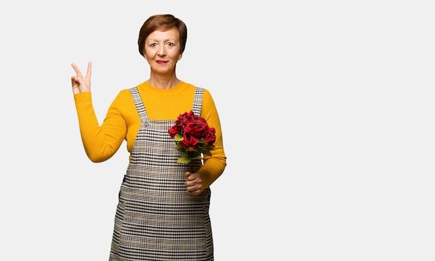 Mittlere gealterte frau, die den valentinsgrußtag tut, der eine geste des sieges tut