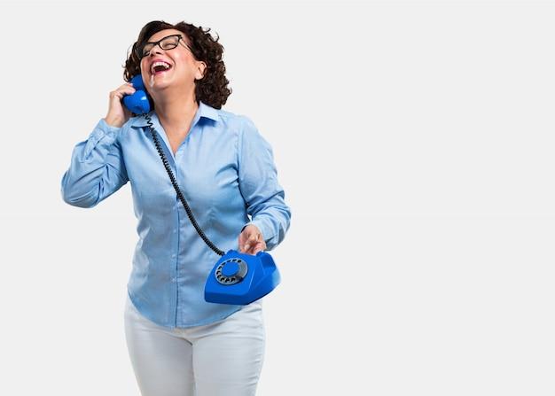 Mittlere gealterte frau, die laut lacht, spaß mit dem gespräch hat und einen freund oder einen kunden anruft