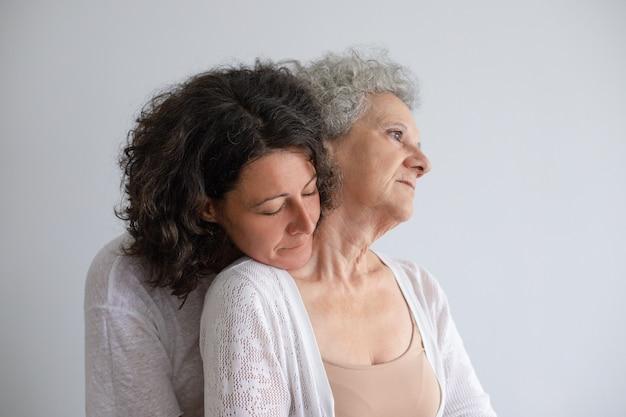 Mittlere gealterte tochter, die ältere mutter umarmt