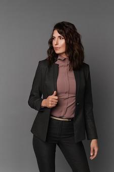 Mittlere geschäftsfrau in einem dunklen anzug und einer rosa seidenbluse gegen das graue oberflächenkonzept von geschäftskleidung für besprechungen und spaziergänge