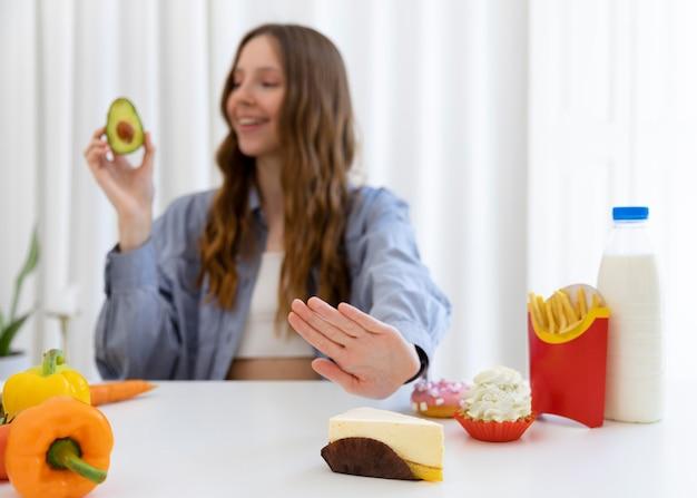 Mittlere geschossene frau mit avocado holding