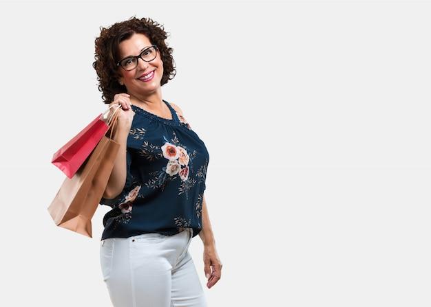 Mittlere greisin nett und lächelnd, sehr aufgeregt, einkaufstaschen tragend, bereiten vor, um zu gehen und nach neuen angeboten zu suchen