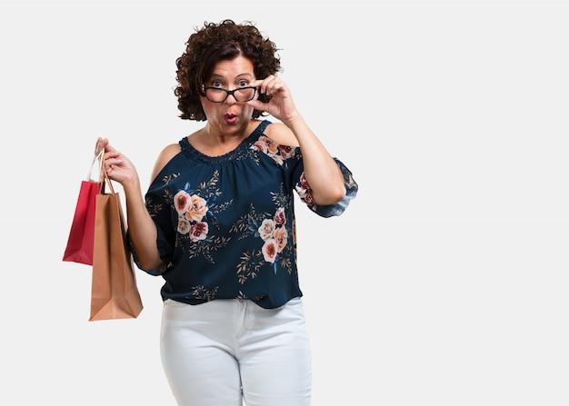 Mittlere greisin nett und lächelnd, sehr aufgeregt, einkaufstaschen tragend