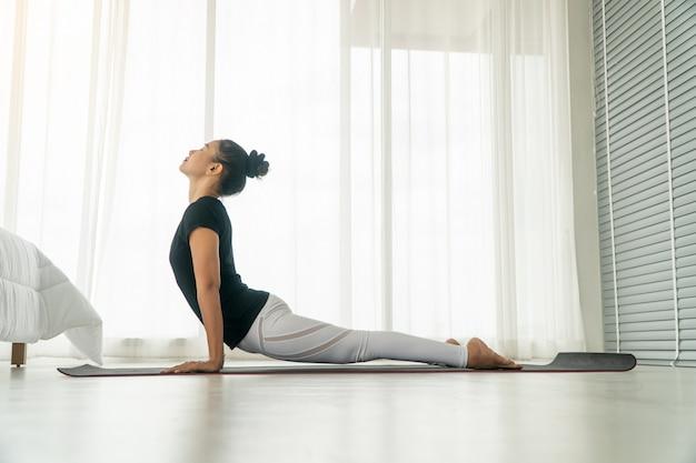 Mittlere greisinnen, die am morgen yoga im schlafzimmer tun