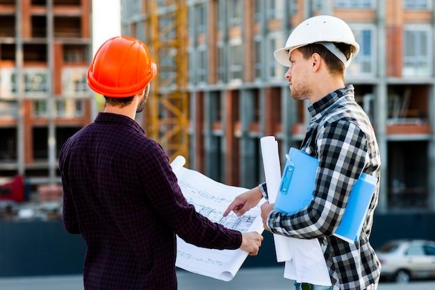 Mittlere hintere ansicht des ingenieurs und des architekten, die bau überwachen