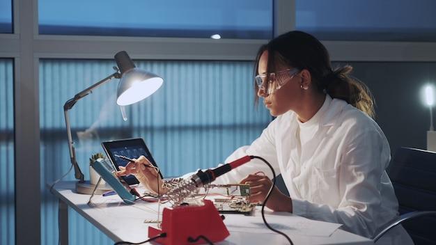 Mittlere nahaufnahme des afroamerikanischen elektronikingenieurs in der schutzbrille, die motherboard mit multimetertester prüft