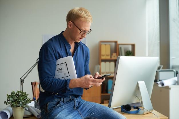 Mittlere nahaufnahme des blonden mannes simsend zum kunden, der auf dem schreibtisch hockt