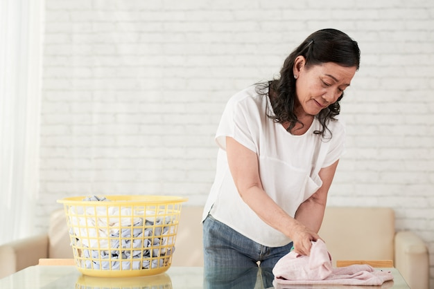 Mittlere nahaufnahme des faltenden hemdes der asiatischen haushälterin nachdem dem bügeln