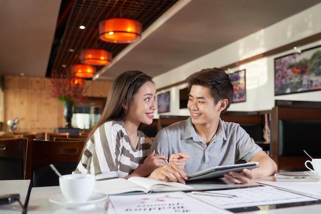 Mittlere nahaufnahme von den jungen asiatischen paaren, die bevorstehende reise nach europa besprechen
