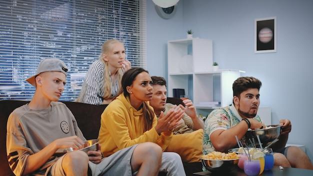 Mittlere nahaufnahme von jungen menschen, die ihre negative reaktion auf aktionen im fernsehen zeigen
