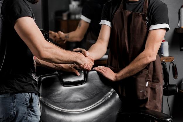 Mittlere schnittansicht eines friseurs, der hand mit männlichem kunden rüttelt
