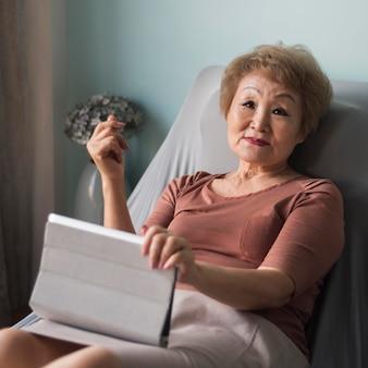 Mittlere schuss alte frau, die tablette hält