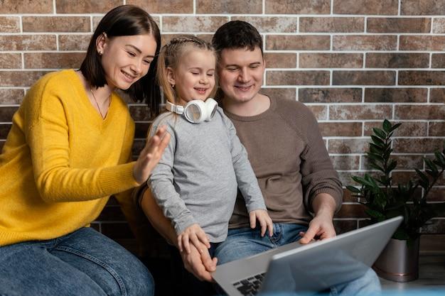 Mittlere schuss glückliche familie mit laptop