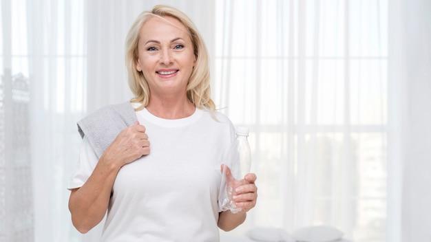 Mittlere schuss glückliche frau mit handtuch und wasserflasche