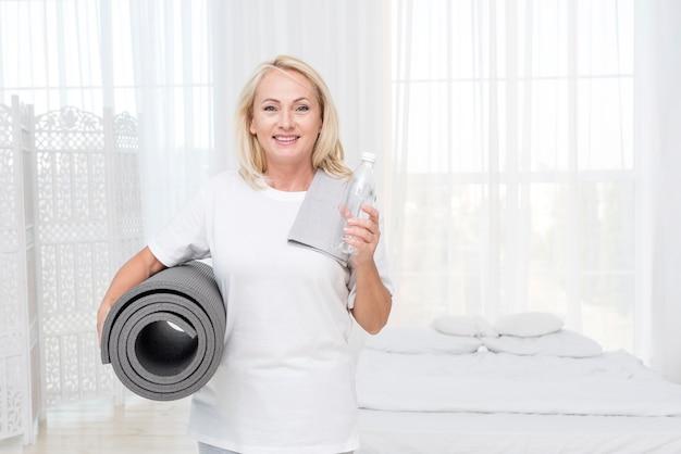 Mittlere schuss glückliche frau mit wasser und yogamatte