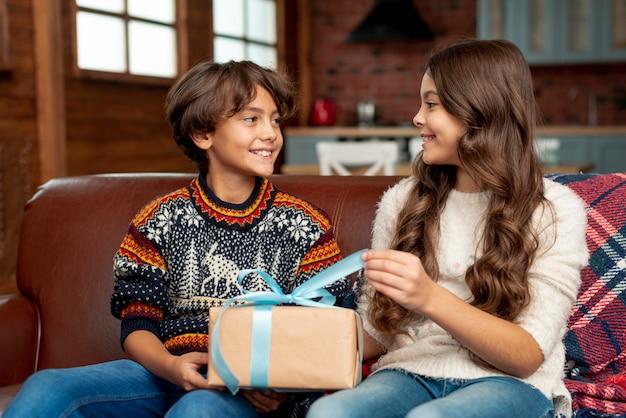 Mittlere schuss glückliche kinder mit geschenk