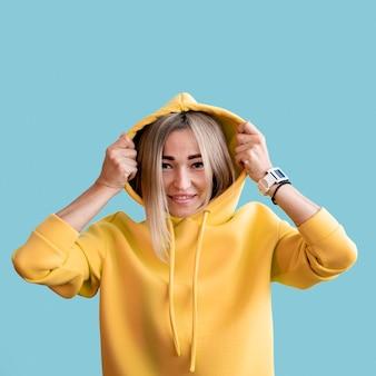 Mittlere schuss smiley asiatische frau, die einen gelben kapuzenpulli trägt