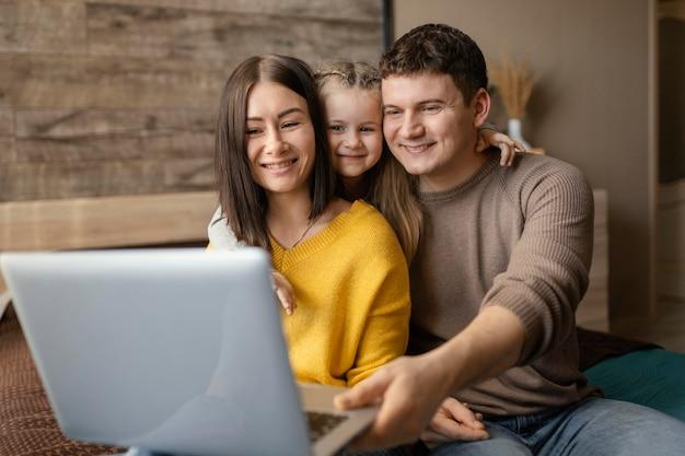 Mittlere schuss-smiley-familie mit laptop