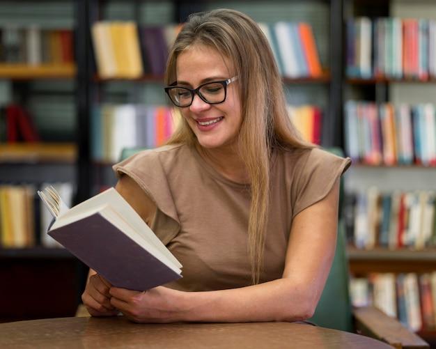 Mittlere schuss-smiley-frau beim lesen