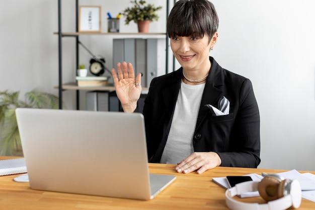 Mittlere schuss-smiley-frau, die am laptop winkt