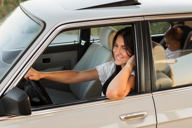 Mittlere schuss-smiley-frau, die im auto aufwirft