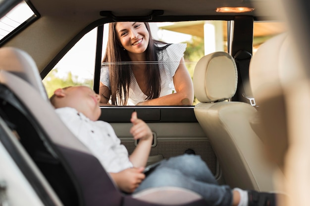 Mittlere schuss-smiley-frau, die kind betrachtet
