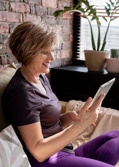 Mittlere schuss-smiley-frau, die tablette hält