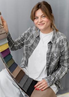 Mittlere schuss-smiley-frau, die textilien hält Kostenlose Fotos