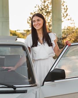 Mittlere schuss-smiley-frau in der nähe des autos