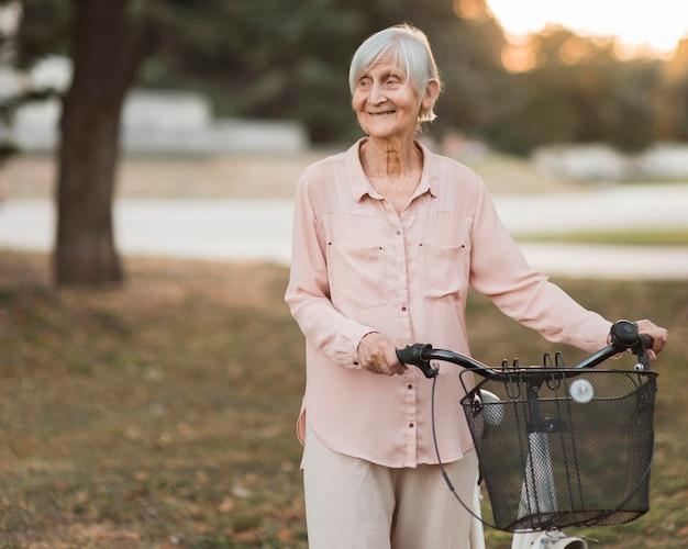 Mittlere schuss-smiley-frau mit fahrrad