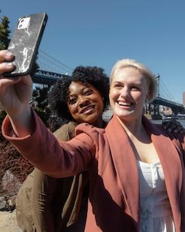 Mittlere schuss-smiley-frauen, die selfie nehmen