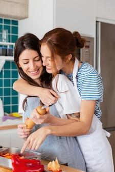 Mittlere schuss-smiley-frauen, die zusammen kochen