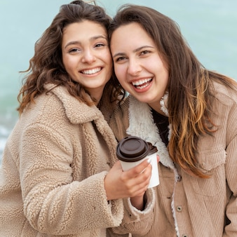 Mittlere schuss-smiley-frauen mit kaffeetassen
