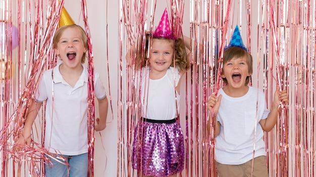 Mittlere schuss-smiley-kinder, die partyhüte tragen