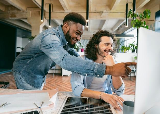 Mittlere schuss-smiley-männer, die computer betrachten