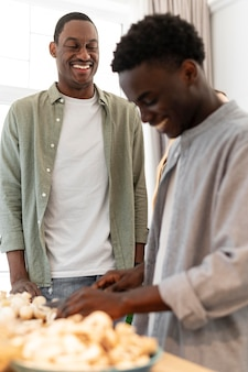 Mittlere schuss-smiley-männer, die zu hause kochen