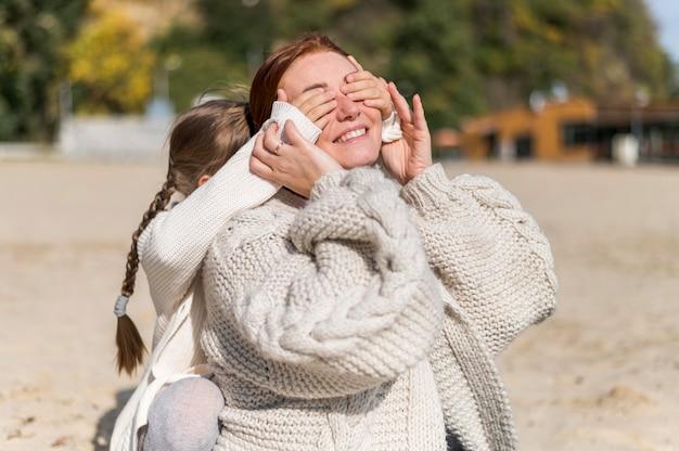 Mittlere schuss smiley mutter und kind am strand
