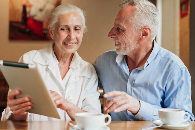 Mittlere schussaltes ehepaar mit einem tablet