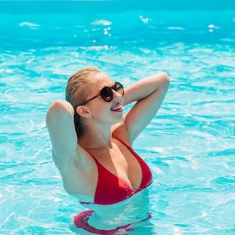 Mittlere schussblondine am pool