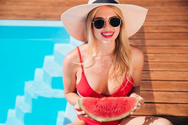Mittlere schussblondine, die eine wassermelone halten