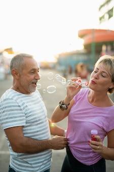 Mittlere schusserwachsene mit seifenblasenhersteller