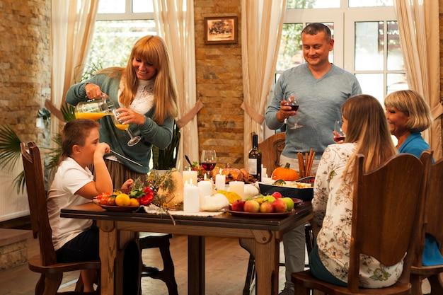 Mittlere schussfamilie, die am tisch sitzt