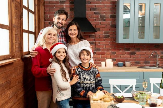 Mittlere schussfamilie, die in der küche sich versammelt