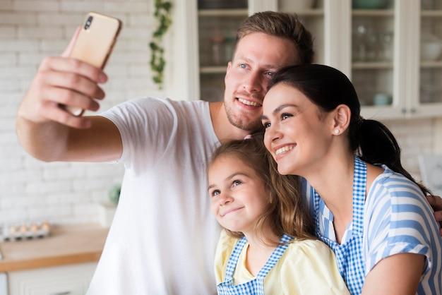 Mittlere schussfamilie, die selfie in der küche nimmt