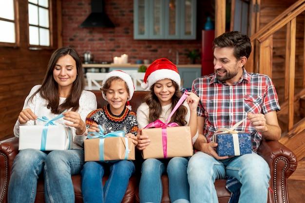 Mittlere schussfamilienmitglieder mit geschenken auf dem sofa