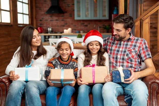 Mittlere schussfamilienmitglieder mit geschenken auf der couch