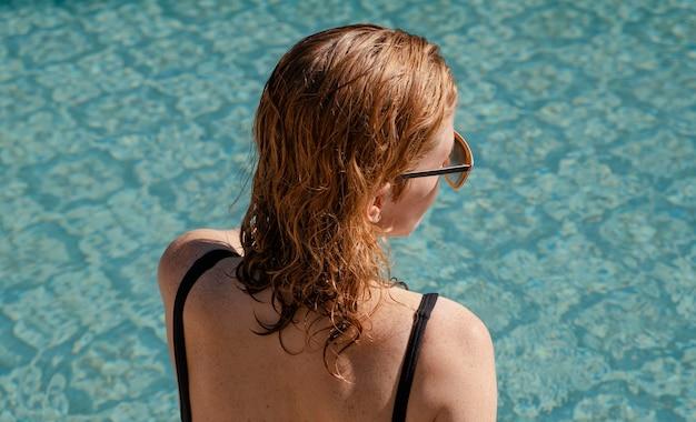 Mittlere schussfrau am pool