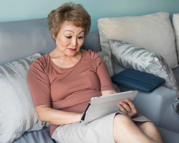 Mittlere schussfrau auf der couch, die tablette hält