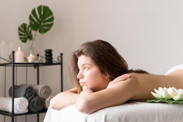 Mittlere schussfrau auf massagetisch